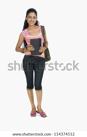 Portrait of a young girl carrying a bag and books - stock photo