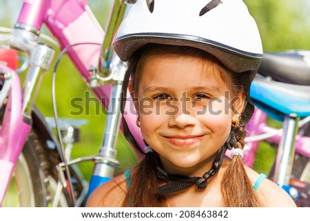 Portrait of a young girl in helmet with bike