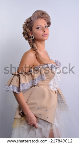 Portrait of a young girl in medieval clothes on a light background.makeup.fashion. - stock photo