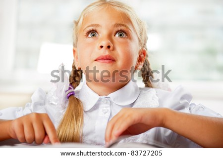 Portrait of a young girl in school at the desk. Horizontal Shot. She is very excited by book, daydreaming - stock photo