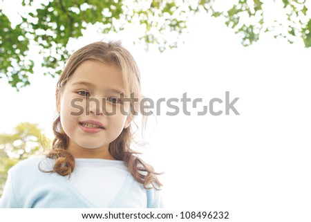 Portrait of a young girl in the park smiling at the camera. - stock photo