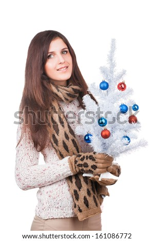 Portrait of a young girl in white sweater with christmas tree in hands, d - stock photo