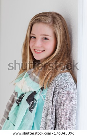 portrait of a young girl leaning on a wall - stock photo