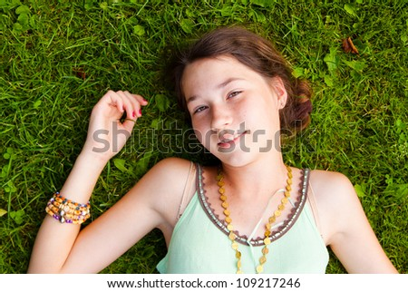 Portrait of a young girl lying down on grass in the park - stock photo