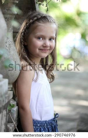 Portrait of a young girl on the background of an old ladder - stock photo