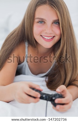 Portrait of a young girl playing video games while she is lying on her bed - stock photo