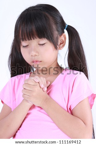Portrait of a young girl praying against a white background