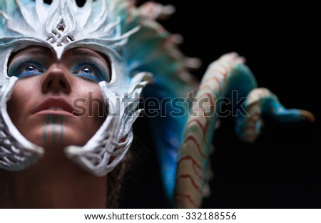 Portrait of a young girl, sad , thoughtful , yearning with blue shiny eyes  looking up, warior strong, brave,with dark complexion, wearing a helmet - mask with horns  - stock photo