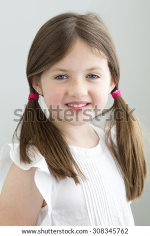 Portrait of a young girl. She has her hair in pigtails and is smiling at the camera against a plain background - stock photo