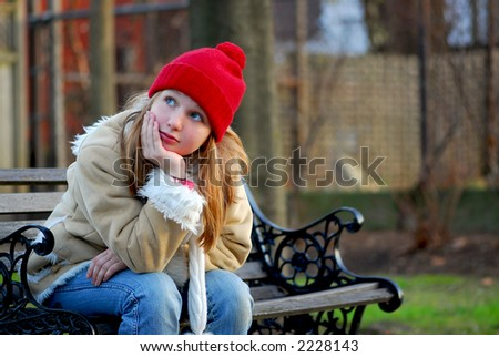 Portrait of a young girl sitting on a bench
