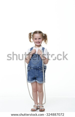 Portrait of a young girl skipping with a white background. She is wearing casual clothing and looking at the camera and smiling. - stock photo