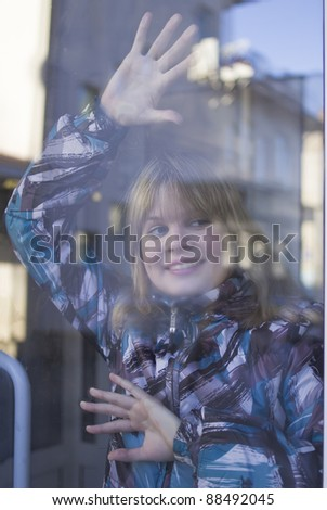 Portrait of a young girl through a window glass - stock photo