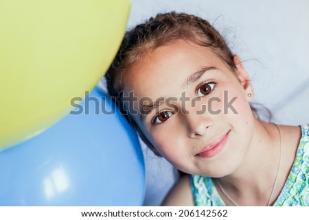 portrait of a young girl with a yellow and blue ball - stock photo