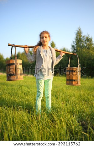 Portrait of a young girl with a yoke and wooden pails - stock photo