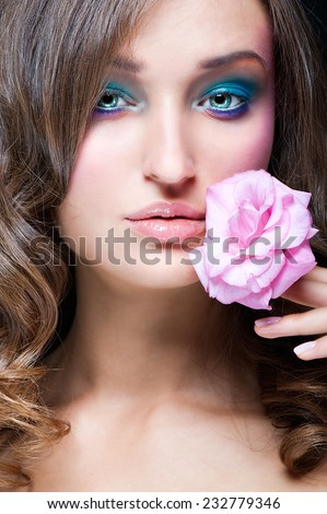 Portrait of a young girl with an unusually beautiful makeup. Blue eyeshadow. Pink flower. - stock photo