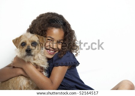 Portrait of a young girl with dreadlocks and frizzy hair, hugging a small dog. White background.