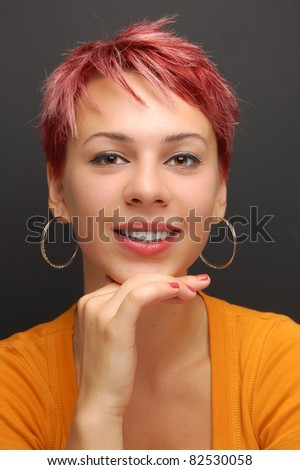 portrait of a young girl with red hair in front of a gray background - stock photo
