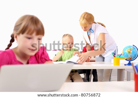 Portrait of a young girl working on laptop at school at the desk. - stock photo