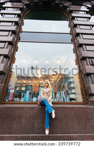 Portrait of a young gorgeous woman posing while sitting outdoors on a shop sill during her recreation time, beautiful female with trendy look relaxing after strolling outside during autumn weekends   - stock photo