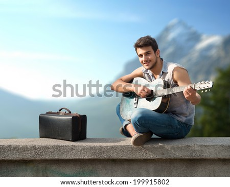 Portrait of a young guitarist sitting on parapet and smiling at camera - stock photo