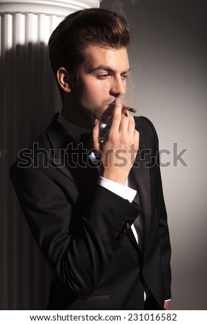 Portrait of a young handsome business man smoking a cigarette and enjoying it.