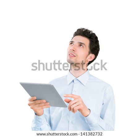 Portrait of a young handsome businessman holding tablet computer and looking up. Isolated on white background