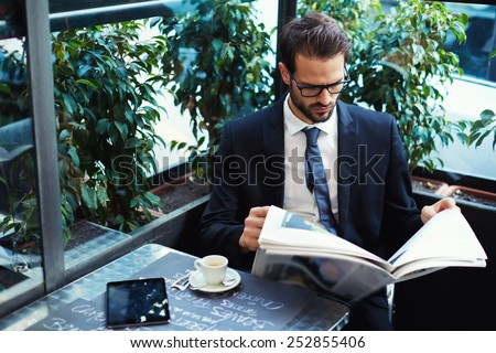 Portrait of a young handsome businessman reading a newspaper at his breakfast in coffee shop, brunette business man holding open newspaper sitting in cafe - stock photo