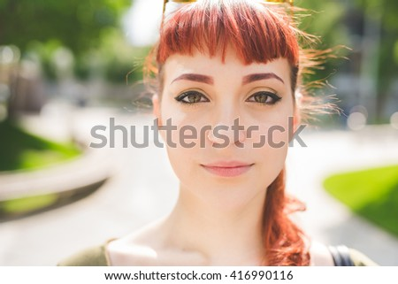 portrait of a young handsome caucasian redhead woman looking in camera, serene - serenity, carefree concept - stock photo