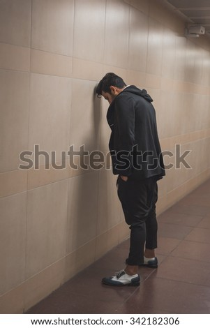 Portrait of a young handsome Indian man posing in a metro station - stock photo