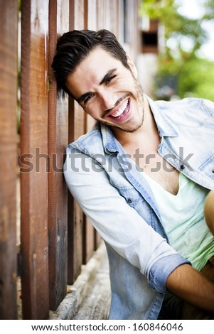 Portrait of a young handsome man, fashion model, with toupee in urban background