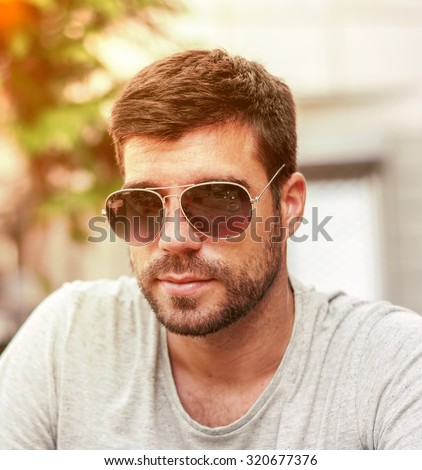 Portrait of a young handsome man, model of fashion, wearing tinted sunglasses in city with burning sun  - stock photo