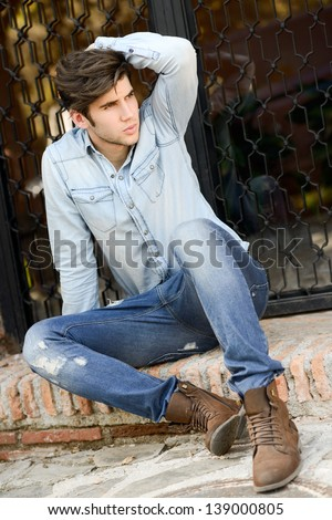Portrait of a young handsome man, model of fashion, with modern hairstyle in urban background