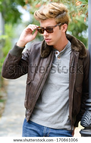 Portrait of a young handsome man, model of fashion, with modern hairstyle in urban background wearing sunglasses. Blonde hair - stock photo