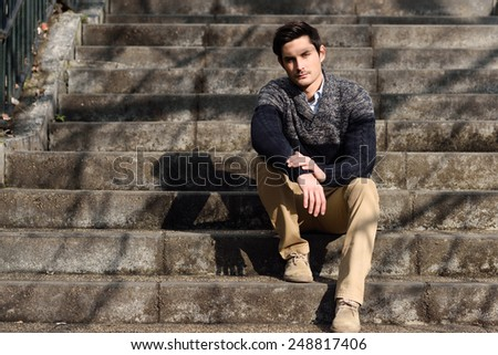 Portrait of a young handsome man, model of fashion, with modern hairstyle sitting on stairs, wearing casual clothes.