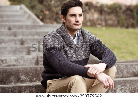 Portrait of a young handsome man, model of fashion, with modern hairstyle sitting on stairs, wearing casual clothes. - stock photo
