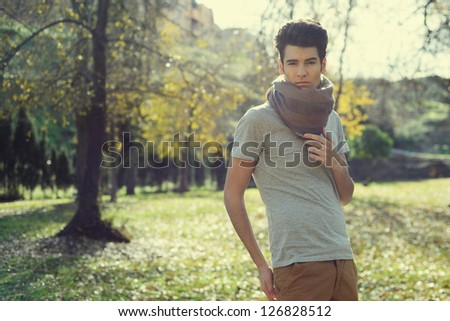 Portrait of a young handsome man, model of fashion, with toupee in the park - stock photo