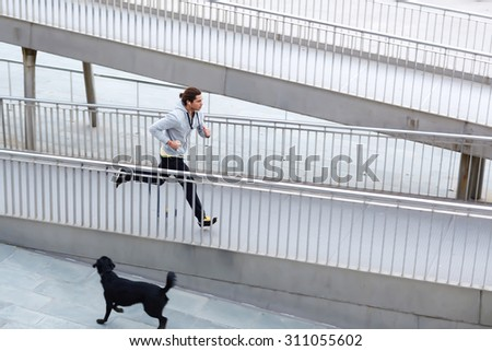 Portrait of a young handsome man runner listening to music with headphones jogging in the street with copy space area for your text message or information,fit men engaged in physical exercise outdoors - stock photo