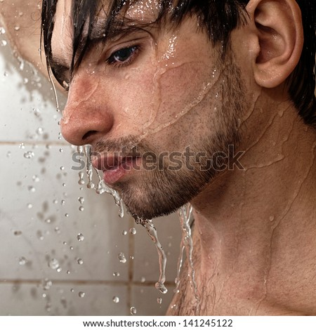 Portrait of a young handsome man takes a shower closeup - stock photo