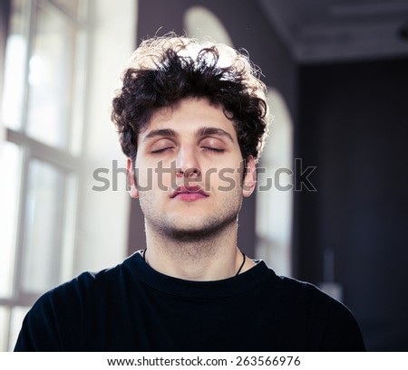 Portrait of a young handsome man with closed eyes - stock photo