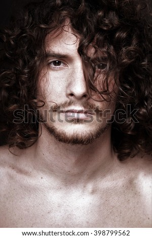 portrait of a young handsome man with curly hair - stock photo