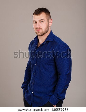Portrait of a young handsome musculed business man wearing blue shirt