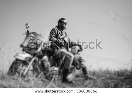 Portrait of a young happy biker with beard sitting on his cruiser motorcycle. Man is wearing leather jacket and blue jeans. Low point of view. Tilt shift lens blur effect. black and white - stock photo