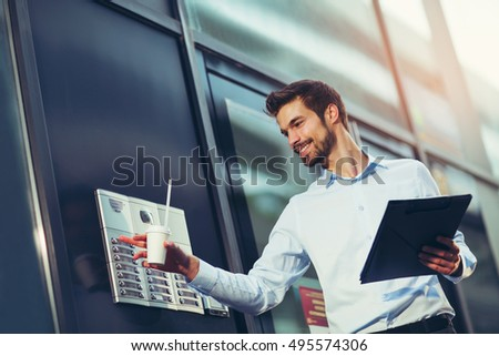 Portrait of a young happy businessman outside the office building, enters the building