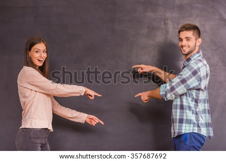 Portrait of a young happy couple, expression of emotions, gray background - stock photo