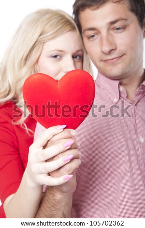 Portrait of a young happy couple holding a red heart.