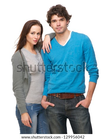 Portrait of a young happy couple standing against white background - stock photo