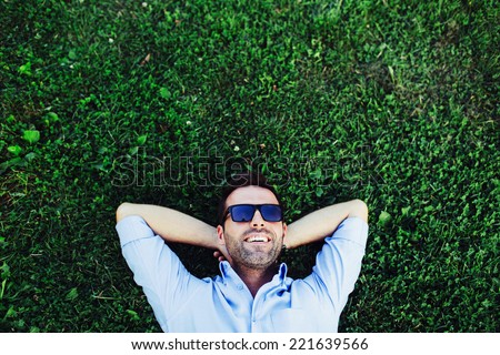 Portrait of a young happy man relaxing on the grass with his hands under the head - stock photo