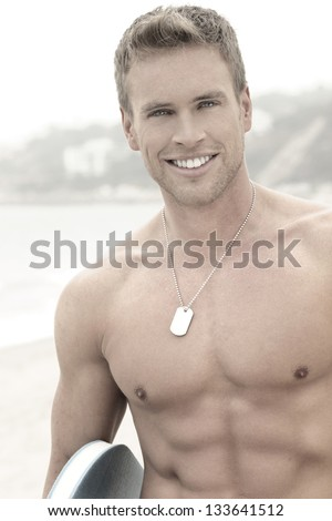 Portrait of a young happy smiling handsome man at the beach - stock photo