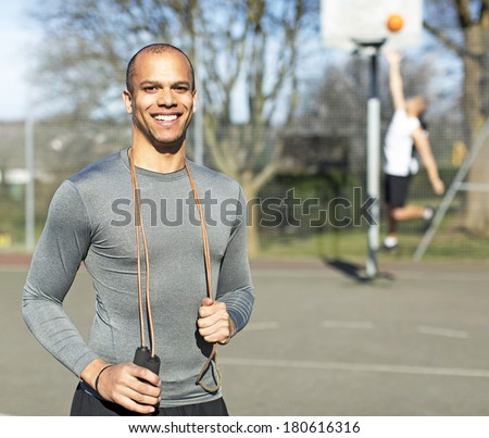 Portrait of a young healthy man holding a skipping jump rope and smiling to camera - stock photo