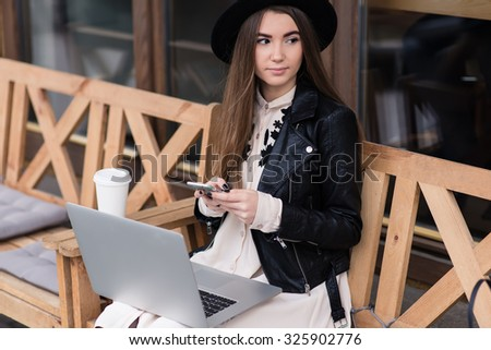 Portrait of a young hipster girl chatting on mobile phone while sitting with laptop computer on a wooden bench of coffee shop, stylish woman using cell telephone while resting after work on net-book - stock photo